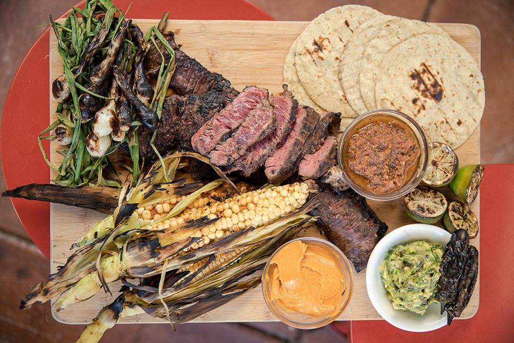 skirt steak, tortillas, fire roasted salsa, charred guacamole and corn on the cob